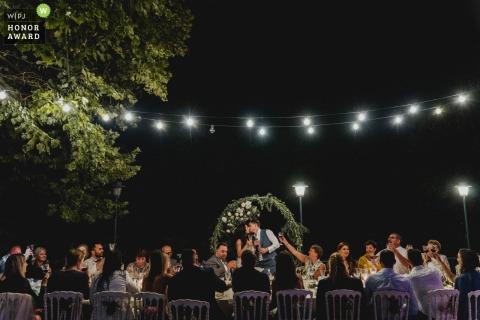 Campania fotógrafo de bodas disparando recepción nocturna en el lago como