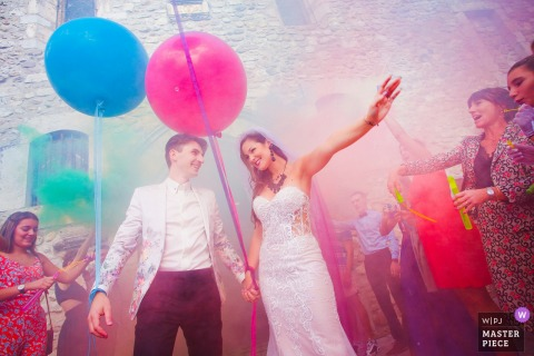France wedding photography of the bride and groom exiting a church with colorful balloons.
