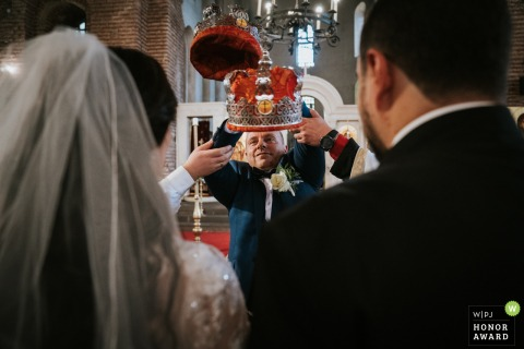 St Sofia church, Sofia wedding ceremony picture | The two priests are helping the best man to put the church crowns on the newlyweds's heads