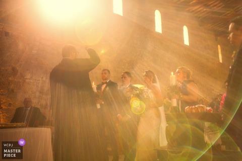 Fotograf ślubny dla Abbazii San Giusto - światło słoneczne oświetla parę podczas błogosławieństwa