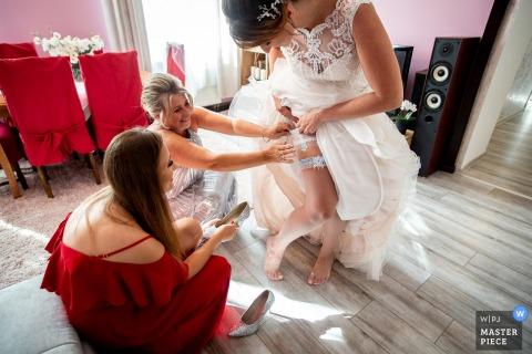Das Haus der Braut, Lodz, Polen Hochzeitsfotograf - Die Brautjungfer und die Mutter der Braut legen traditionell Banknoten hinter das Strumpfband.