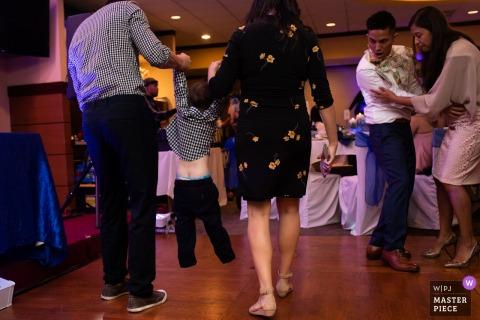 Neues Hafenrestaurant in Cupertino | Hochzeitsfotograf | Das Kind wird von den Eltern aus der Tanzfläche gezogen