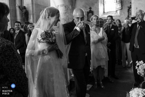 Photographe de cérémonie de mariage à Ambazac. Père embrasse sa fille dans l'église