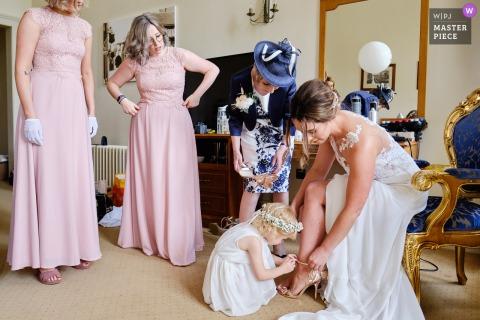 Stoke Rochford Hall, Grantham, Royaume-Uni | Photographe de reportage de mariage | La petite fille de fleur est catégorique qu'elle veut attacher les chaussures de la mariée.
