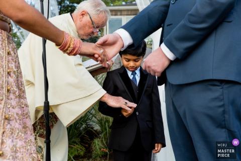 Photographie de mariage montrant un garçon avec des bagues lors d'une cérémonie au Soundview Caterers, à Bayville Long Island, lors d'une cérémonie