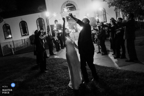 Photographe de mariage de la bibliothèque historique de Redondo Beach - Les jeunes mariés jouent avec leurs feux de Bengale à la fin de la nuit de leur mariage.
