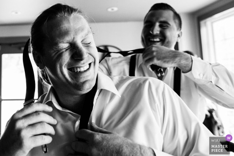 Groomsman helps another groomsman put his suspenders on at Bear Brook Valley NJ wedding - New Jersey Wedding Photojournalism