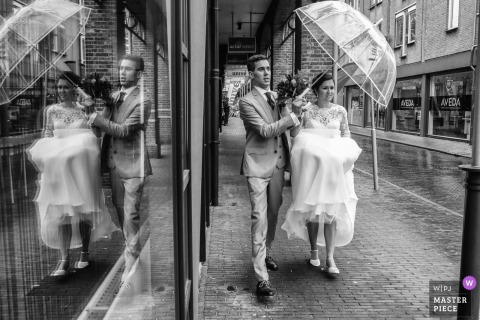 Amersfoort wedding reportage photography - walking in the rain to the church with just one umbrella