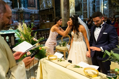 Santa Maria Church in Rome wedding photo | Multiple action during the ceremony...bride getting tear wiped and groom inspecting his new ring.