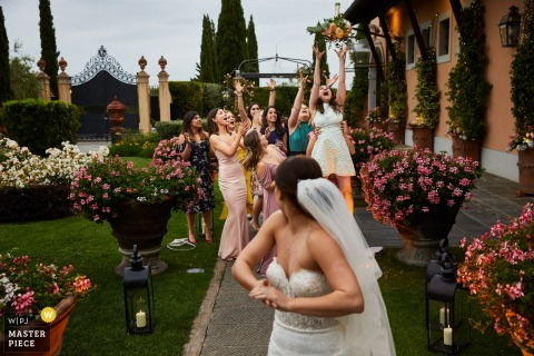 Toskania, Włochy zabawa weselna - Zdjęcie panny młodej podrzucającej bukiet do druhen na zewnątrz