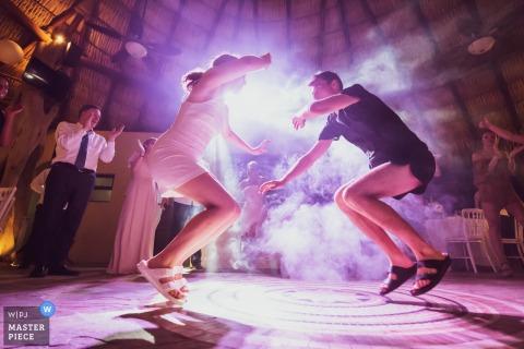 Las Palmas, Santa Cruz Huatulco, Oaxaca, Meksyk - Fotoreportaż ślubny - Narzeczeni wydają się lewitować podczas tańca podczas burzy podczas przyjęcia.