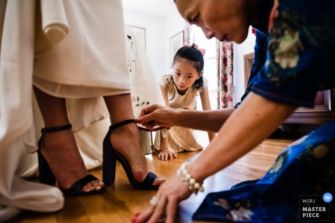 Wedding photography from bride getting ready in East Burke, Vermont - The flower girl looks on as the bride gets help with her shoes.