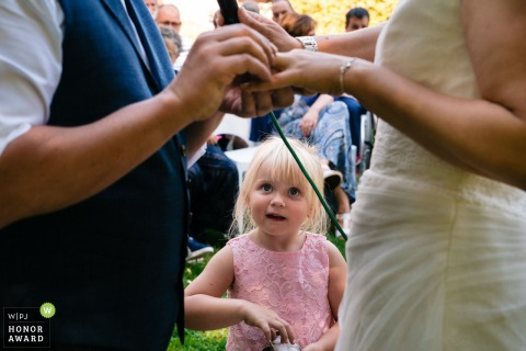 Flanders wedding photographer at Outdoor Wedding Ceremony  Photo: Daughter of the bride and groom who was also the ring bearer, looks in awe while her dad and mom exchange rings