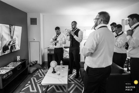 Fotoperiodismo de bodas en el hotel Baronette Renaissance Detroit-Novi: los padrinos de boda necesitan un video para ayudarlos a hacer un doble nudo de Windsor.
