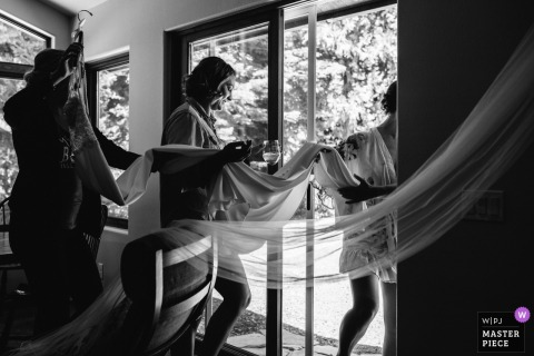 Tahoe Vista, CA: Private Home Wedding Day Photography - Bridesmaids carry the bride's dress.