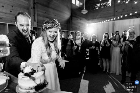 Sugarloaf Mountain, Maine Trouwlocatiefotograaf - Een bruid en bruidegom snijden de taart met hun handen tijdens hun Sugarloaf Mountain-bruiloft in Maine.