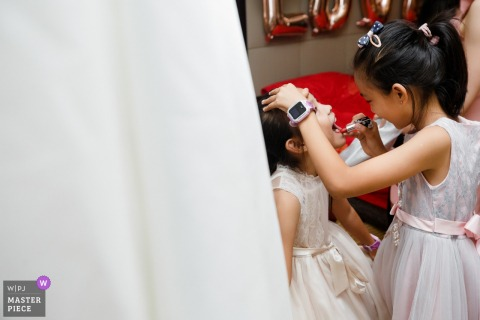 Fujian, China Wedding Photojournalism - Flower Girls putting on Lipstick