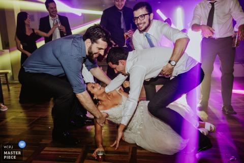 Porto Alegre, Hochzeitsfotografie Casa da Figueira der gefallenen Braut mit den Gästen und Bräutigam, die ihr oben helfen.