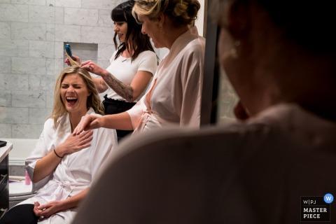 Photographie de l'hôtel Colorado le jour du mariage - Mariée qui rit avec des demoiselles d'honneur pendant la préparation de la mariée