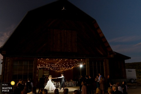Colorado Reception Venue Photography - Bride and groom share first dance at sunset - lit barn photos at night.