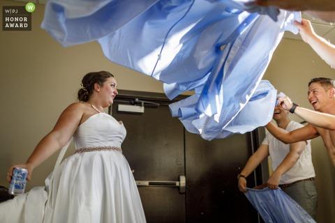 City Park Pavilion, Denver, CO wedding venue picture | Groomsmen fan the bride to cool her off after the outdoor ceremony at the City Park Pavilion in Denver.