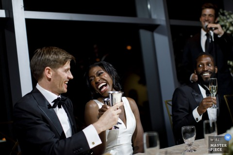 De bruid en bruidegom lachen tijdens een toast in het Denver Museum of Nature and Science - Colorado Wedding Photographer