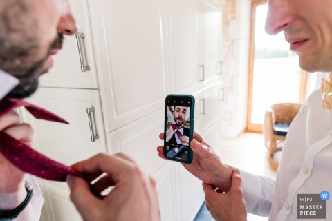 wedding photography in Bergerac, France - the groom makes his bow tie looking at himself in his smartphone