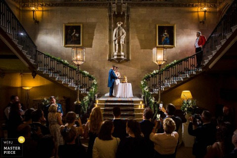 Ashridge House, United Kingdom Wedding Photographer — Cutting the Cake on the stairs with guests watching