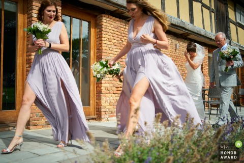 Oak Barn, Frame Farm, Kent wedding venue reportage-style photo | Bridesmaids lead the bride a her father to the wedding ceremony