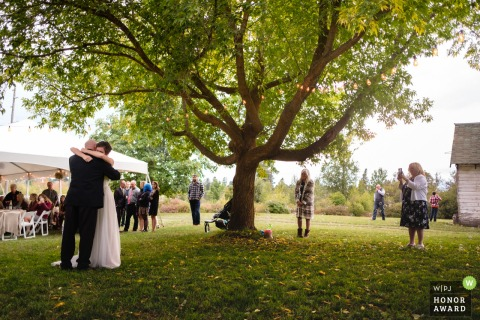 Brides family farm wedding photography | The ceremony and reception near Kalispell Montana | The bride and her father share a hug at the end of their father daughter dance.