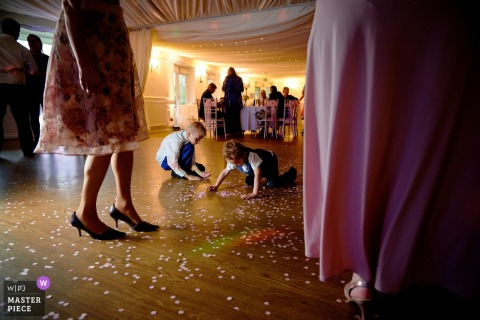England Reception venue photography — Kids are being kids, picking the confetti
