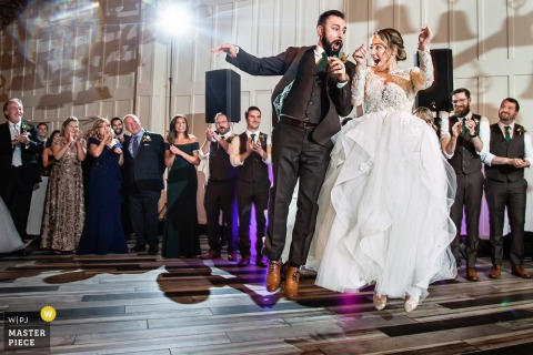 Wedding Reception Venue - Bride and Groom jump together right after being ontroduced into the reception