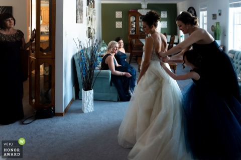 Wedding photo from a Private house, Edmonton, AB, Canada | Bridesmaid and the daughter of the bride helping the bride put the dress on. Mother of the bride and the bridesmaids are watching.