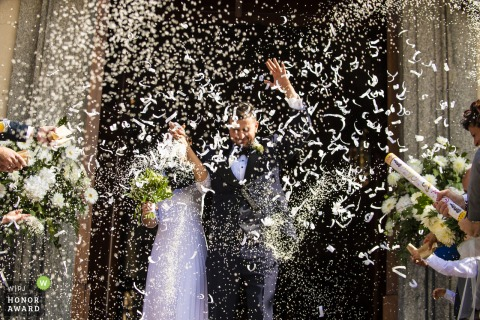 Lecco Lombardy wedding photographer captured the bride and groom exiting under confetti cannons