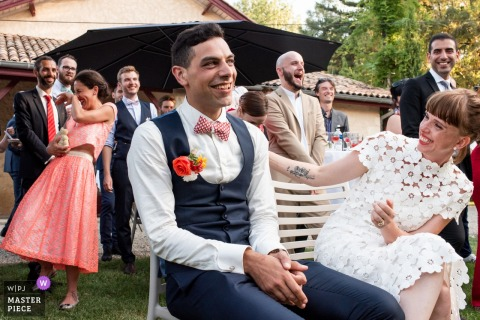 ChâteauPeyrèredu Tertre婚礼仪式上新郎在会谈中笑的照片。
