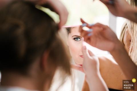 安大略省新娘家的婚礼当天摄影-发型师在她的头发上工作时,新娘在镜子里偷看自己的妆