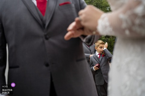 Hazlehurst House Mcdonough Georgia - wedding photographer - Ring bearer wipes away tears while the ring is put on