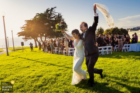 Redondo Beach Historic Library Hochzeitsort Bild der Braut und des Bräutigams, die zujubeln, während sie ihre Hochzeitszeremonie verlassen.