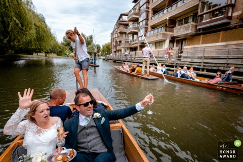 Cambridge, UK wedding reportage photographer: Bride and Groom punting on the Cam