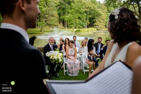 Illinois wedding photo from a Private house, Chicago  Ceremony image showing the bride and groom exchanging vows by the pond