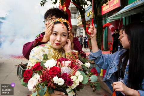 Fujian, China wedding day photo of the bride's ears being covered as firecrackers explode and smoke fills the air.
