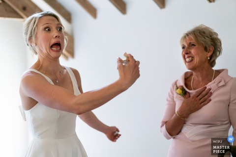 wedding photography at Warborne Farm, New Forest, Hampshire — Bride Laura pulling a face whilst applying finishing touch of perfume in front of her mother.