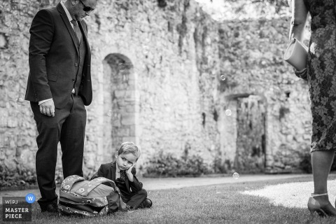 Beaulieu Abbey, Hampshire wedding photo os a young boy with his head in his hands at his father's feet. The look of boredom upon his face, but he may well have been disciplined.