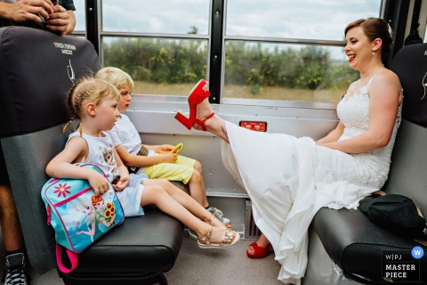 Vinska fontana Marezige	wedding photographer — Bride is showing her shoes to kids.