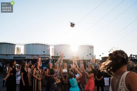 Frankfurt, Loft EInswedding venue photo of the bride throwing toss | bouquet in the air overhead