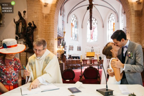 Flanders wedding reportage photography at the Church | the wedding couple shares a kiss right after siging the book in church