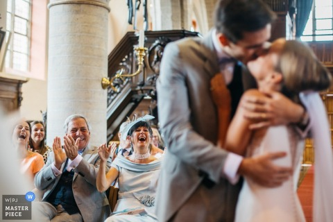 "Flanders Church wedding photographer — the couple kisses right after the priest declared ""the couple may kiss as ling as people applaud"""