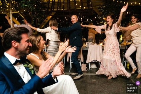Flanders Wedding Reception Photography | Bride and groom cheer their guests while they're doing a crazy conga