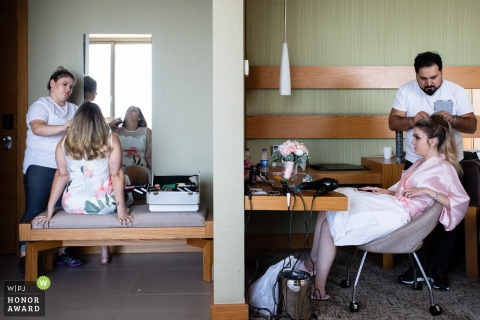 Turkey wedding photojournalism at the hotel	| The bride and sister getting their hair and makeup done in hotel room