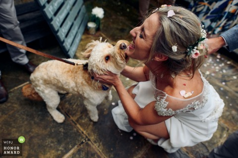 Tuddenham Mill, UK wedding photo of Bride and her dog kissing